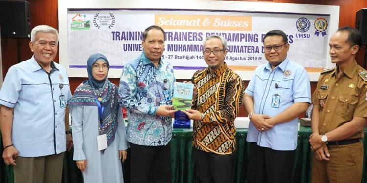 Rektor UMSU Dr Agussani MAP ( Ketiga Kiri) menyerahkan cinderamata kepada Pembicara Sekretaris Jenderal Forum BUMDes Indonesia Rudy Suryanto SE MAcc AK CA (ketiga kanan) (Foto umsu.ac.id/M Syafii)